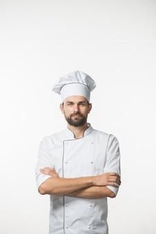 Cuoco maschio professionista in uniforme bianca del cuoco unico che si leva in piedi contro la priorità bassa bianca