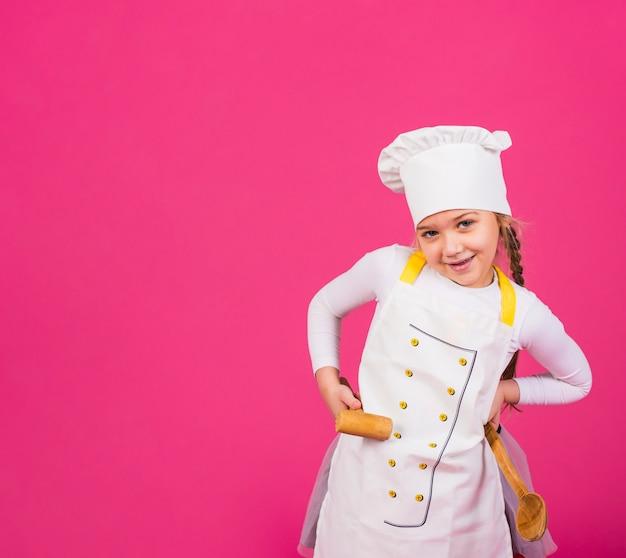Cuoco sveglio della ragazza che sta con gli utensili della cucina