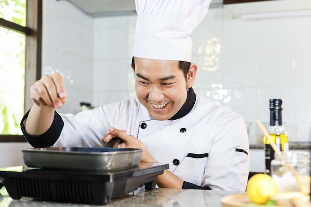 Cuoco unico asiatico che cucina nel ristorante della cucina