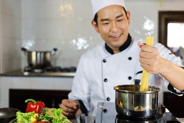Cuoco unico asiatico dell'uomo che cucina alimento in ristorante