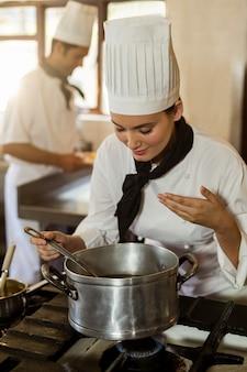 Cuoco unico capo sorridente che si mescola nella cottura del vaso