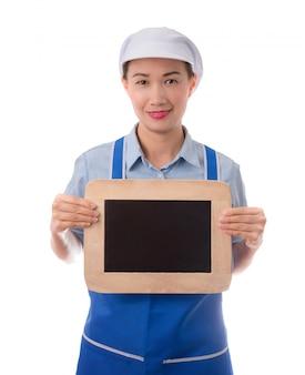Cuoco unico, casalinga che mostra la lavagna in bianco del segno del menu o il segno in bianco.