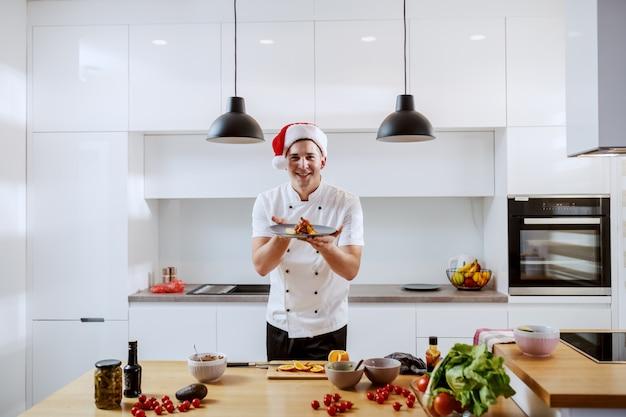 Cuoco unico caucasico attraente allegro in uniforme e con il cappello di santa sulla testa