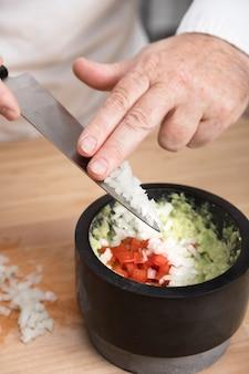 Cuoco unico che aggiunge cipolla nel guacamole