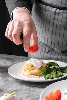 Cuoco unico che aggiunge gli ultimi ritocchi al piatto