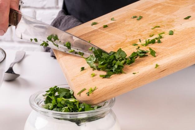 Cuoco unico che aggiunge l'erba cipollina tritata al condimento