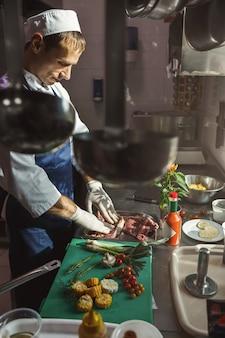 Cuoco unico che cucina bistecca sulla cucina del ristorante