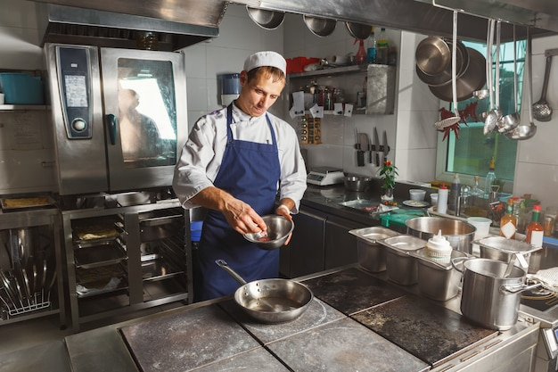 Cuoco unico che cucina carne al ristorante o alla cucina dell'hotel