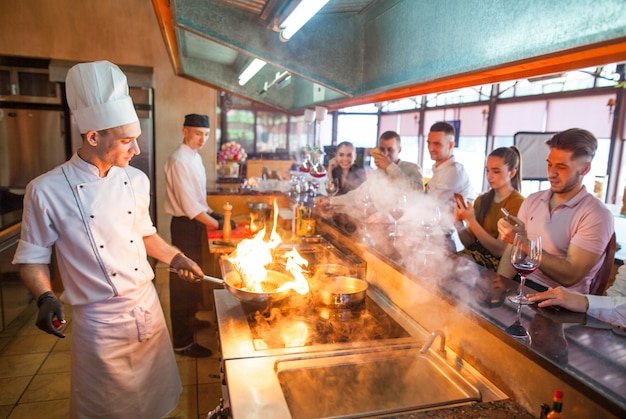 Cuoco unico che cucina frutti di mare in un ristorante.