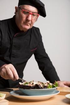 Cuoco unico che cucina insalata con i funghi