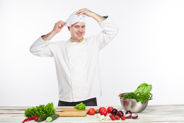 Cuoco unico che cucina l'insalata della verdura fresca nella sua cucina