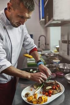 Cuoco unico che cucina la bistecca di manzo succosa alla cucina del ristorante