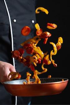Cuoco unico che cucina le verdure su una vaschetta.