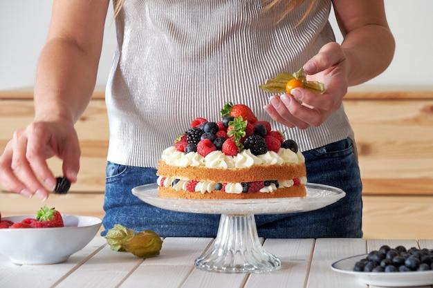Cuoco unico che decora la torta frutti di bosco