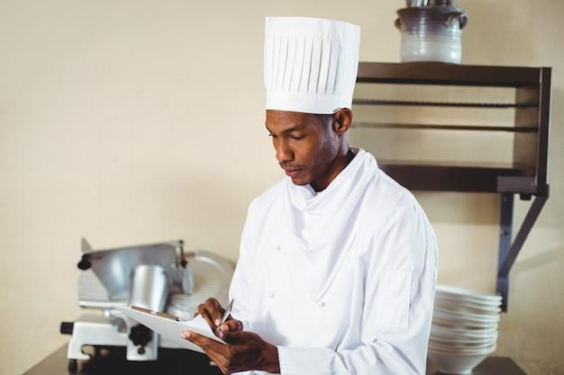 Cuoco unico che fa le note su una lavagna per appunti