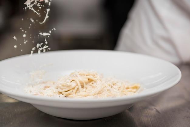 Cuoco unico che gratta formaggio sugli spaghetti