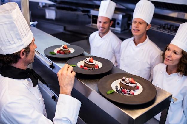 Cuoco unico che ispeziona i piatti da dessert sopra alla stazione di ordine