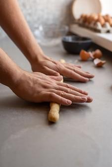 Cuoco unico che modella pasta con entrambe le mani