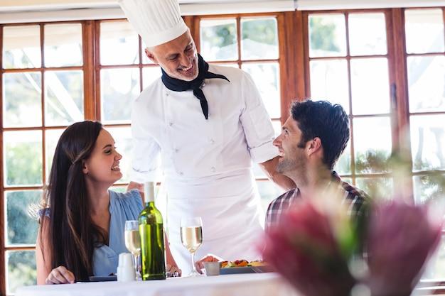 Cuoco unico che parla con coppia al ristorante