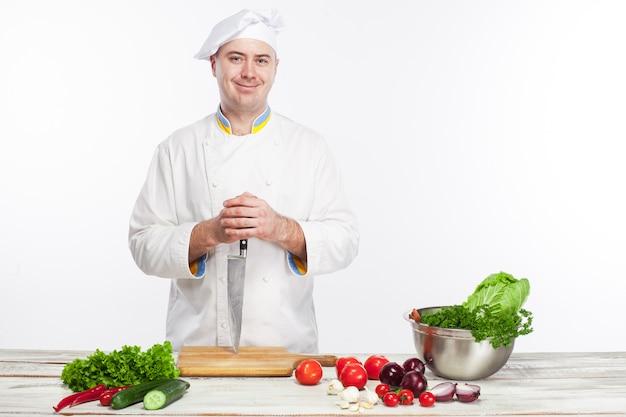 Cuoco unico che posa con il coltello nella sua cucina