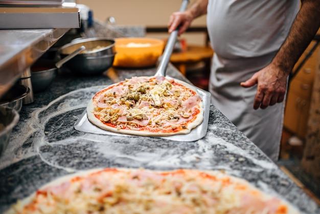 Cuoco unico che prende la pizza cruda sulla pala del metallo per cuocere nel forno.