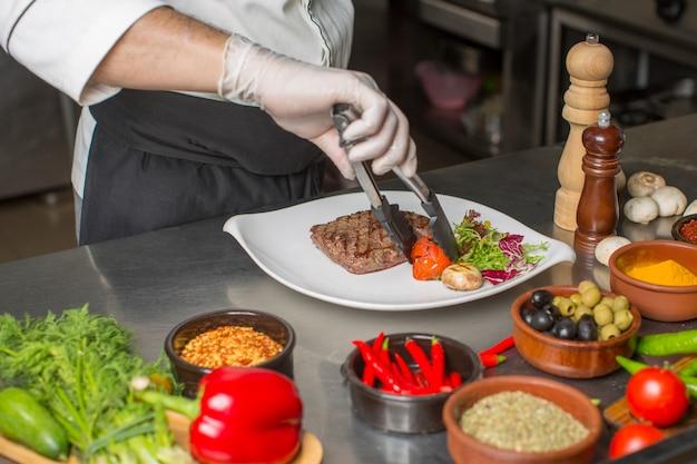 Cuoco unico che prepara la bistecca di manzo per il servizio con insalata e verdure grigliate