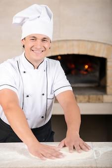 Cuoco unico che prepara pasticceria nella sua cucina.