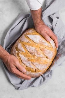 Cuoco unico che si tiene per mano sul pane rotondo
