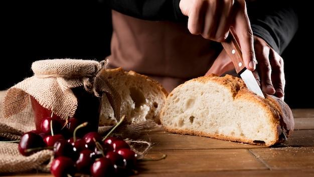 Cuoco unico che taglia il pane con vasetto di marmellata di ciliegie