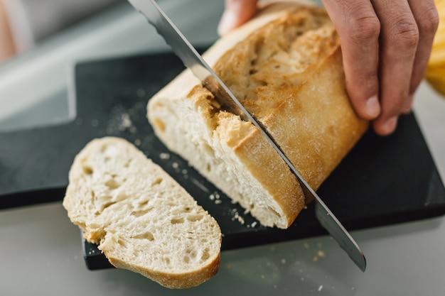 Cuoco unico che taglia pane italiano fresco