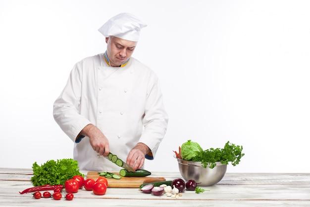 Cuoco unico che taglia un cetriolo verde nella sua cucina
