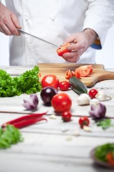 Cuoco unico che taglia un pomodoro rosso la sua cucina