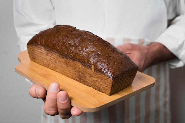 Cuoco unico che tiene delizioso pane dolce