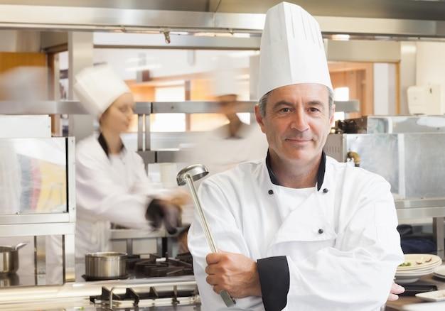 Cuoco unico che tiene la siviera mentre sorride