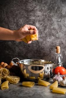Cuoco unico che tiene pasta a forma di grande