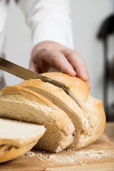 Cuoco unico del primo piano che affetta pane