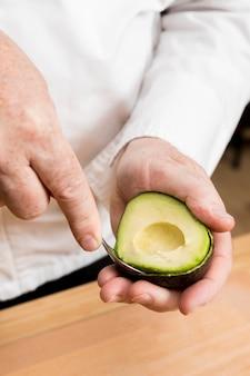 Cuoco unico del primo piano che cucina avocado