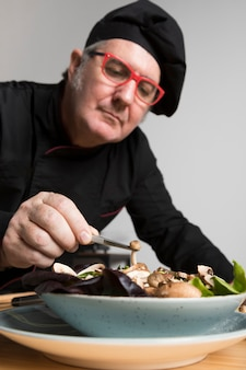 Cuoco unico di angolo basso che cucina insalata con i funghi