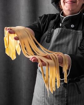 Cuoco unico di smiley che tiene pasta fresca