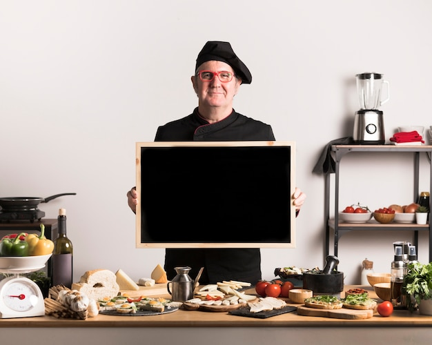 Cuoco unico di vista frontale che tiene blocco per grafici in bianco