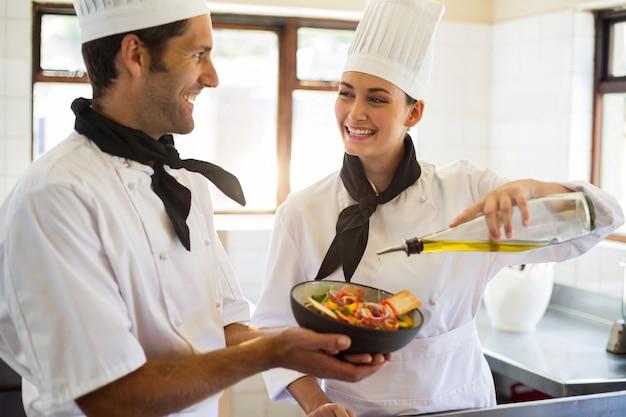 Cuoco unico felice che versa olio d'oliva su insalata