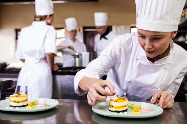 Cuoco unico femminile che guarnisce i dessert deliziosi in un piatto