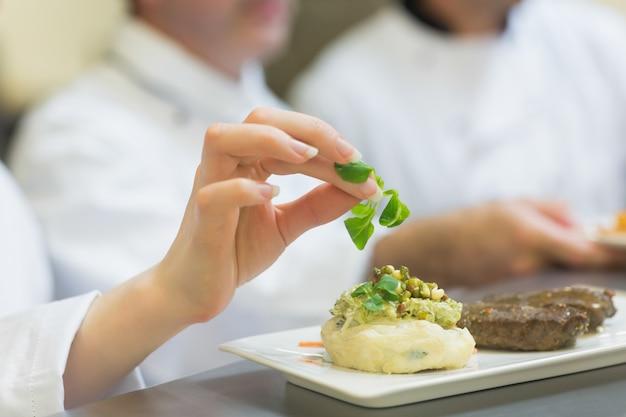 Cuoco unico femminile che guarnisce un piatto con bistecca