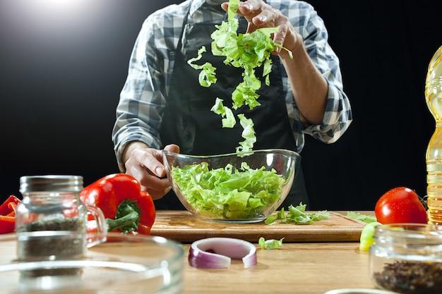 Cuoco unico femminile che taglia gli ortaggi freschi