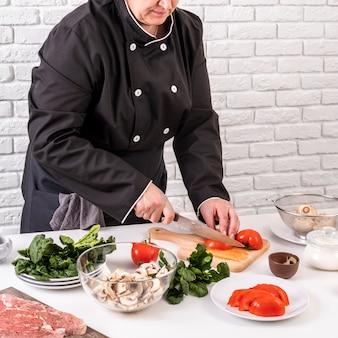 Cuoco unico femminile che taglia i pomodori a pezzi per il piatto