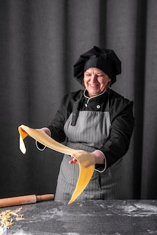 Cuoco unico femminile che tiene foglio di pasta