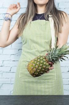 Cuoco unico femminile che tiene un ananas in mano