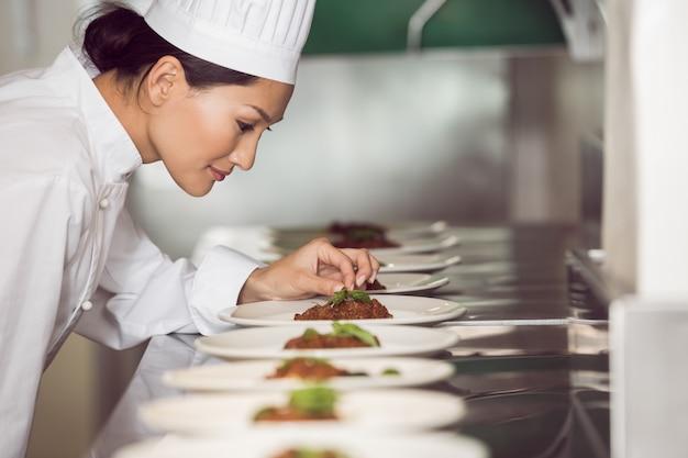 Cuoco unico femminile concentrato che guarnisce alimento in cucina