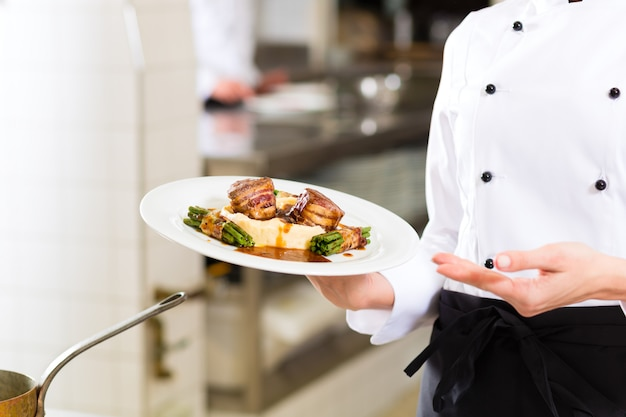 Cuoco unico femminile nella cottura della cucina del ristorante