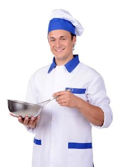 Cuoco unico in uniforme bianca e cappello con padella della cucina.